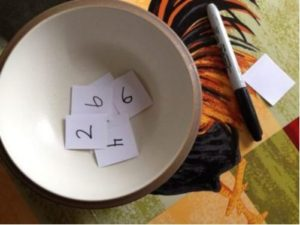 Small bowl with numbered pieces of paper inside