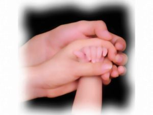 young child's hand grasped by parents' hands