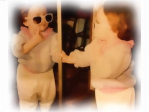 toddler in sunglasses looking at reflection in mirror