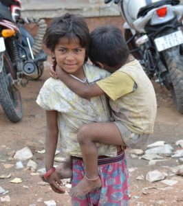 a young poor Pakistani girl holds her little brother in her arms