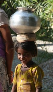 A young child balances a container of water on her head.