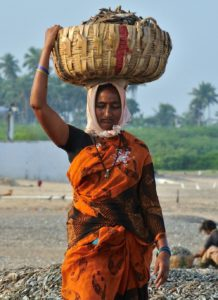 A masi carries a load of wood chips in a basket balanced on her head.