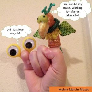 hand holding Melvin, a bird finger puppet, and Martha, a small plastic large eyed finger puppet