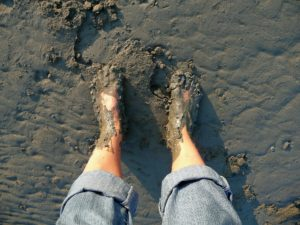 Barefoot woman standing in a muddy pit