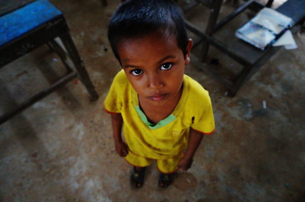 A small child looks forlorn up into the camera. He wears a dirty yellow shirt and matching yellow shorts. He stands in a poor classroom on a cold cement floor.