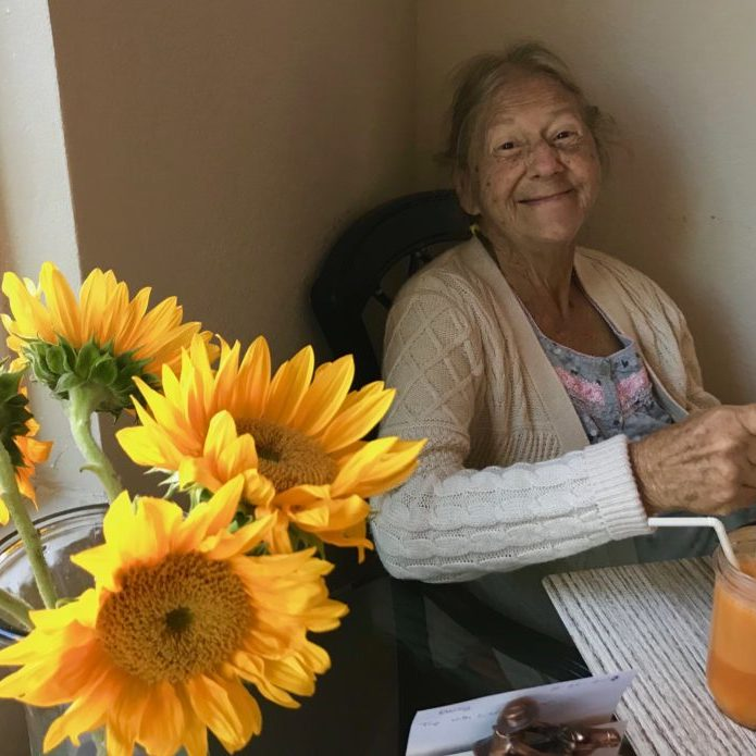Yellow sunflowers in a vase and Mom smiling brightly