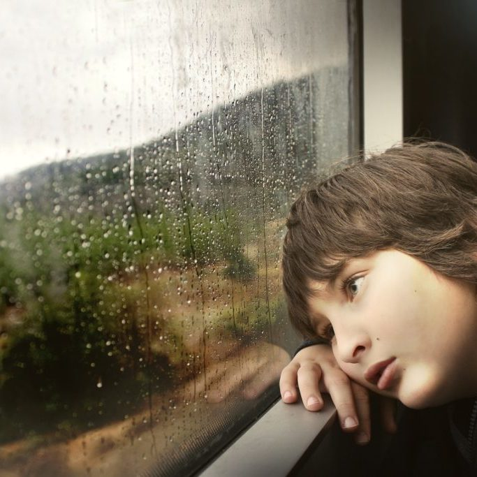 young boy bored raining outside window